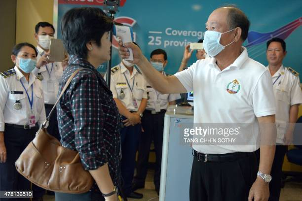 Cambodian Health Minister Mam Bun Heng tests the body temperature of a woman with an infrared thermometer at Phnom Penh International Airport on June...