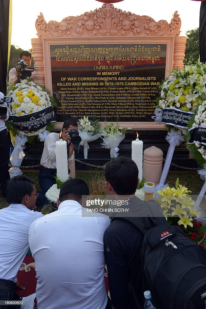 Cambodian journalists pray in front of a memorial sign at a park in front of the Le Royal hotel on February 6, 2013. Cambodia on February 6 officially unveiled a memorial to dozens of foreign and local journalists killed covering the country's 1970-75 war won by the communist Khmer Rouge regime. Led by 'Brother Number One' Pol Pot, who died in 1998, the Khmer Rouge wiped out nearly a quarter of the population through starvation, overwork or execution during its 1975-1979 rule in a bid to forge a communist utopia.