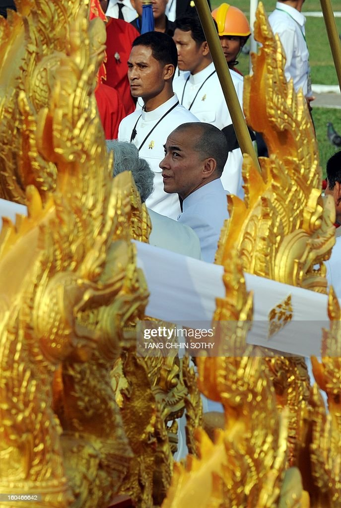 Cambodian King Norodom Sihamoni (C) looks at the royal float (front) during a funeral procession for the late former King Norodom Sihanouk in front of the Royal Palace in Phnom Penh on February 1, 2013. A sea of mourners filled the streets of the Cambodian capital on February 1 for a lavish funeral for revered former king Norodom Sihanouk, who towered over six tumultuous decades in his nation's history.