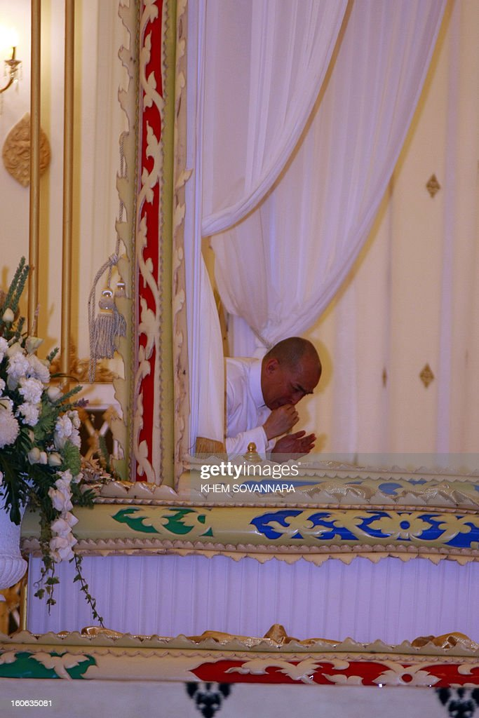 Cambodian King Norodom Sihanouk cries as he prays over the coffin of the late former King Norodom Sihanouk inside the crematorium is placed minutes before his cremation, near the Royal Palace in Phnom Penh on February 4, 2013. Thousands of mourners massed in the Cambodian capital as the kingdom cremated its revered former King Norodom Sihanouk, who steered his country through six turbulent decades. AFP PHOTO/ KHEM SOVANNARA