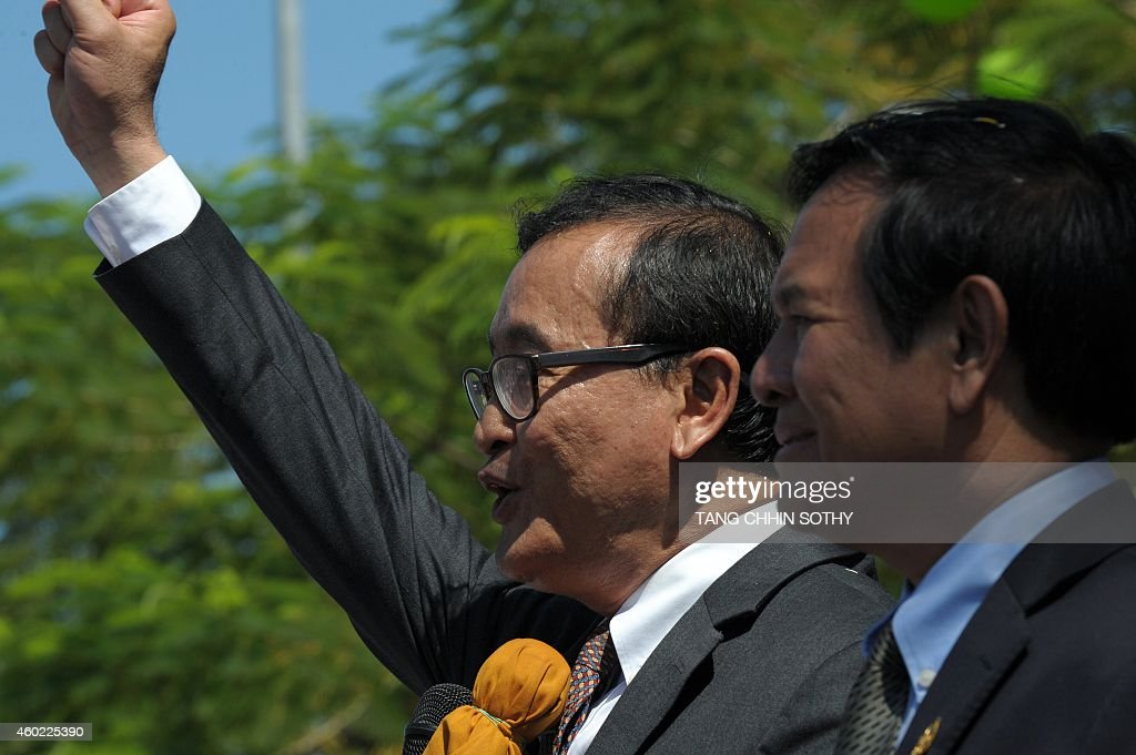 Cambodian lawmaker and opposition Cambodia National Recue Party (CNRP) leader <a gi-track='captionPersonalityLinkClicked' href=/galleries/search?phrase=Sam+Rainsy&family=editorial&specificpeople=660347 ng-click='$event.stopPropagation()'>Sam Rainsy</a> (L) shouts slogans as he makes an address to the public, as deputy of the CNRP and first vice president of National Assembly, <a gi-track='captionPersonalityLinkClicked' href=/galleries/search?phrase=Kem+Sokha&family=editorial&specificpeople=659005 ng-click='$event.stopPropagation()'>Kem Sokha</a> (R), listens in front of the National Assembly building during a rally to mark Human Rights day in Phnom Penh on December 10, 2014. The United Nations proclaimed December 10 as Human Rights Day in 1950 after the UN General Assembly adopted the Universal Declaration of Human Rights two years previously.