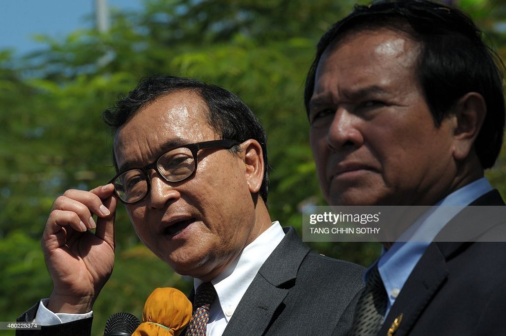 Cambodian lawmaker and opposition Cambodia National Rescue Party (CNRP) leader <a gi-track='captionPersonalityLinkClicked' href=/galleries/search?phrase=Sam+Rainsy&family=editorial&specificpeople=660347 ng-click='$event.stopPropagation()'>Sam Rainsy</a> (2nd R) speaks to people as deputy of the CNRP and first vice president of National Assembly, <a gi-track='captionPersonalityLinkClicked' href=/galleries/search?phrase=Kem+Sokha&family=editorial&specificpeople=659005 ng-click='$event.stopPropagation()'>Kem Sokha</a> (R), listens in front of the National Assembly building during a rally to mark Human Rights day in Phnom Penh on December 10, 2014. The United Nations proclaimed December 10 as Human Rights Day in 1950 after the UN General Assembly adopted the Universal Declaration of Human Rights two years previously.