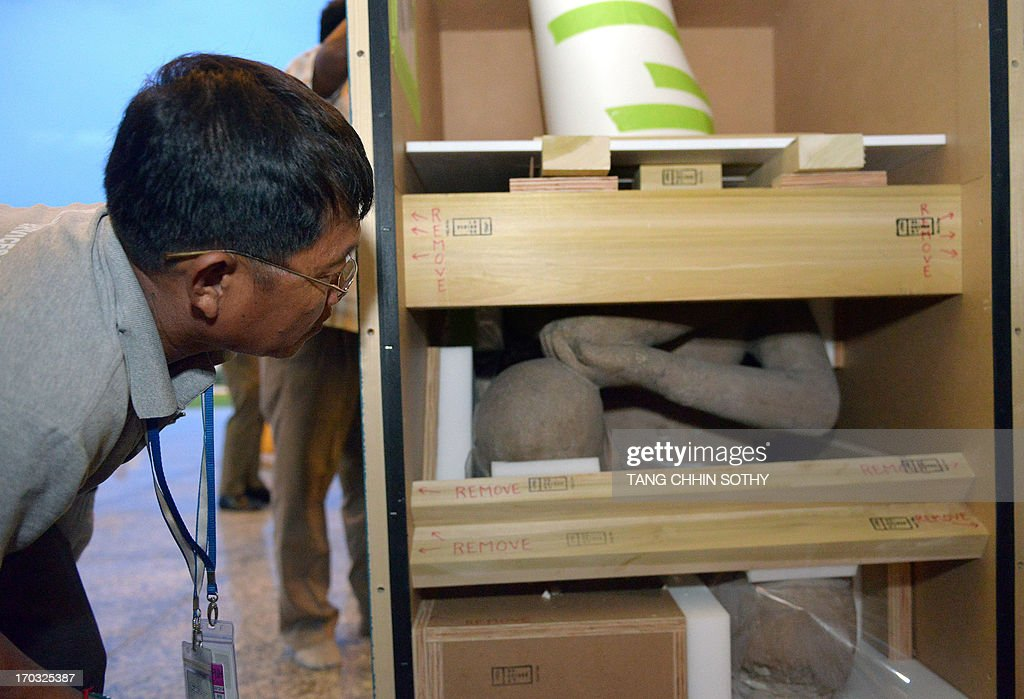 A Cambodian man looks at a statue upon it's arrival at the Phnom Penh International Airport on June 11, 2013. Two 10th century statues that Cambodia says were looted from a jungle temple several decades ago returned home on June 11, from New York's Metropolitan Museum of Art, in what the kingdom described as a 'historic' moment.