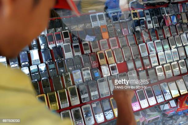 A Cambodian man point at mobile phones at a shop in Phnom Penh on May 12 2010 AFP PHOTO/TANG CHHIN SOTHY / AFP PHOTO / TANG CHHIN Sothy