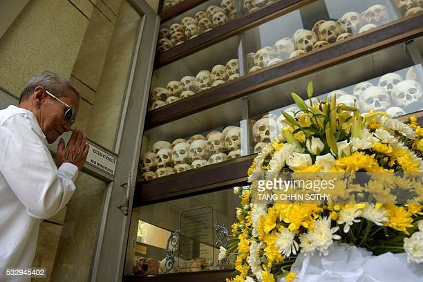 A Cambodian man prays in front of skulls to mark the annual 'Day of Anger' at the Choeung Ek killing fields memorial in Phnom Penh on May 20 2016...