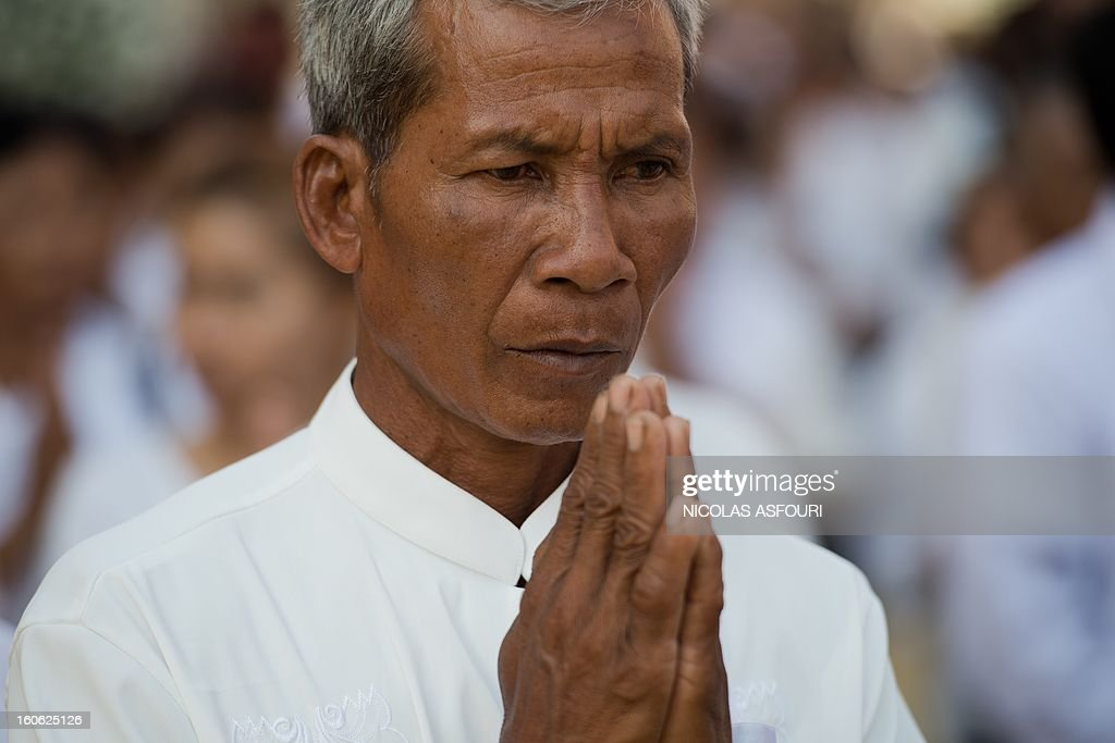 A Cambodian man prays while queuing to enter the crematorium area where the coffin of Cambodia's late king Norodom Sihanouk rests before his cremation near the Royal Palace in Phnom Penh on February 4, 2013. Cambodia was due to hold an elaborate cremation ceremony for its revered former king Norodom Sihanouk, part of a week-long funeral for the colourful late royal. AFP PHOTO / Nicolas ASFOURI