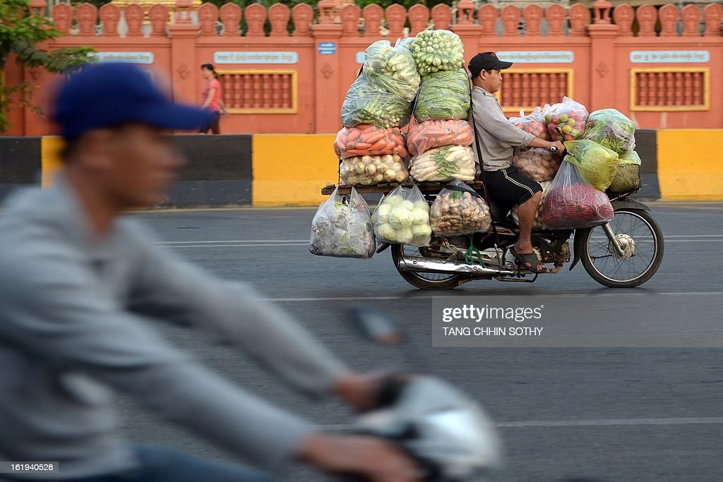 A Cambodian man (R) rides his motorbike loaded with vegetables along a street in Phnom Penh on February 18, 2013. Written off as a failed state after the devastating 1975-1979 Khmer Rouge regime and several decades of civil war, Cambodia remains one of the world's poorest countries with around 30 percent of its 14 million people living on less than a dollar a day.