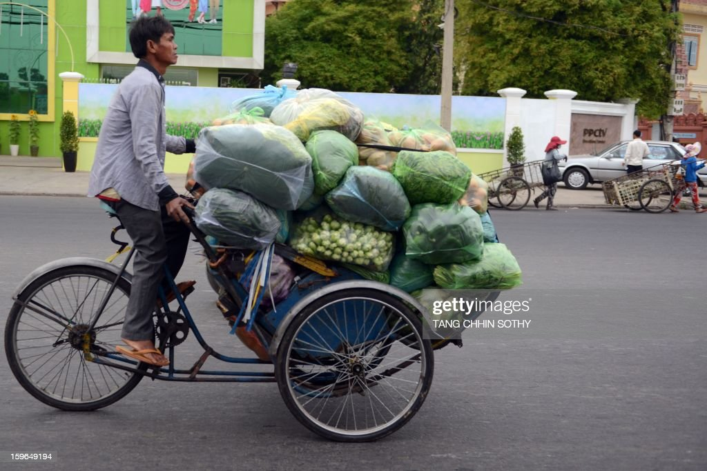 A Cambodian man rides his three-wheel 'cyclos' loaded with vegetables along a street in Phnom Penh on January 18, 2013. The Association of Southeast Asian Nations (ASEAN), which comprises 10 countries, Brunei, Cambodia, Indonesia, Laos, Malaysia, Myanmar, Philippines, Singapore, Thailand and Vietnam have agreed that the Asean Economic Community (AEC) could be launched in 2015.
