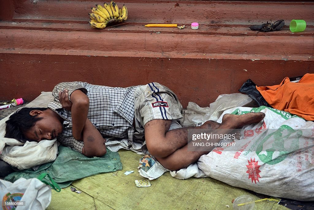 A Cambodian man sleeps amongst litter along a street in Phnom Penh on January 3, 2013. Written off as a failed state after the devastating 1975-1979 Khmer Rouge regime and several decades of civil war, Cambodia has used garment and footwear exports and tourism to help improve its economy, but remains one of the world's poorest countries with around 30 percent of its 14 million people living on less than a dollar a day. AFP PHOTO / TANG CHHIN SOTHY