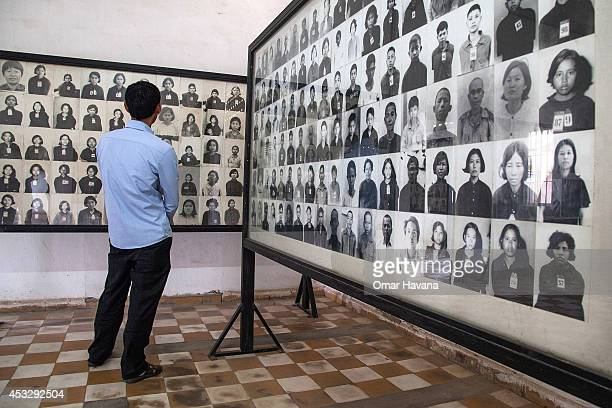 Cambodian man stands by a wall of photographs of prisoners of the Khmer Rouge regime in one of the rooms of Tuol Sleng prison also known as S21 after...