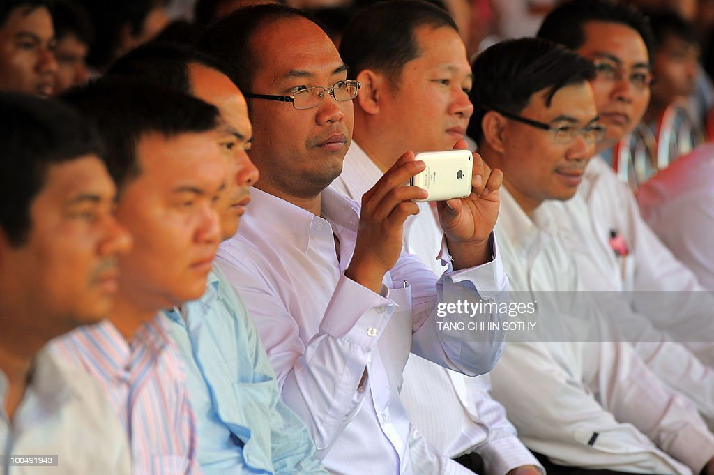 A Cambodian man takes picture with his mobile phone during the day of anger ceremonies at the Choeung Ek killing fields memorial in Phnom Penh on May 20, 2010.