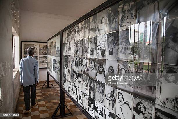 Cambodian man walks across a room filled with photos of dead prisoners in Tuol Sleng prison also known as S21 after the announcement of the verdict...