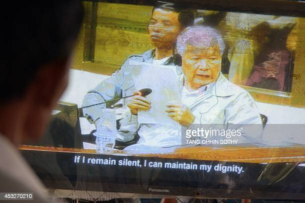 A Cambodian man watches former Khmer Rouge head of state Khieu Samphan on a television as his trial at the Extraordinary Chamber in the Courts of...