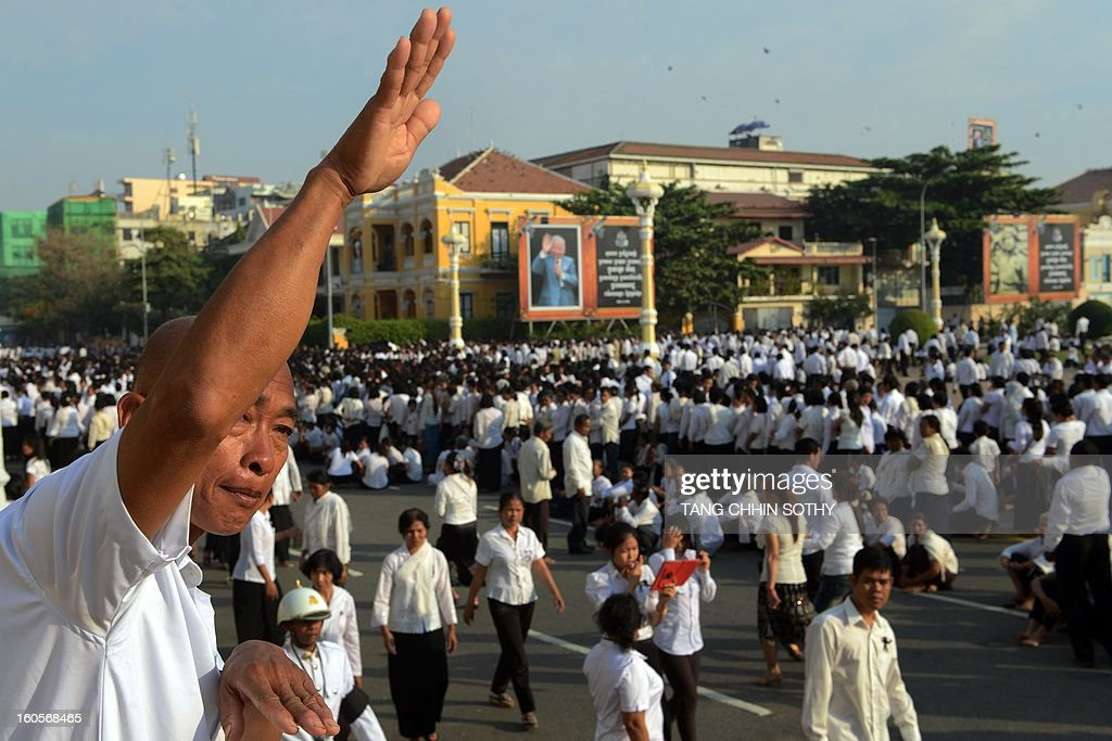 A Cambodian man (L) waves while crowds gather by a portrait of the late former king Norodom Sihanouk (background) in front of the Royal Palace in Phnom Penh on February 3, 2013. Thousands of Cambodians have paid their last respects to their beloved former king Norodom Sihanouk as his body lay in state ahead of his cremation on February 4. AFP PHOTO / TANG CHHIN SOTHY