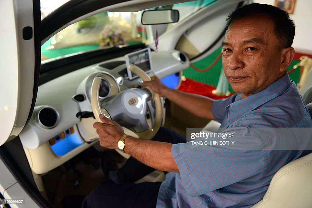 Cambodian mechanic Nhean Phaloek sits in a locally made electric car 'Angkor EV 2013' at a showroom in Phnom Penh on January 8, 2013. Cambodia's Heng Development Company has unvveilled its first electric-powered car branded 'Angkor', named after the country's famed ancient Angkor temples, which has a top speed of 60 kilometres per hour and was designed by local innovator Nhean Phaloek.