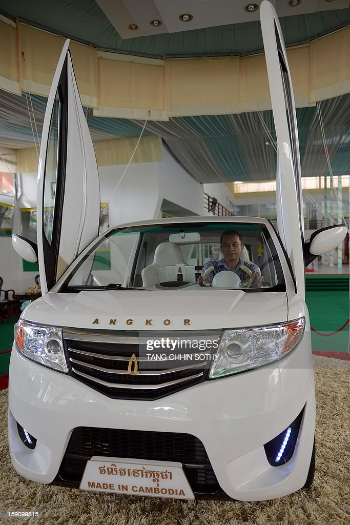 Cambodian mechanic Nhean Phaloek (R) sits in a locally made electric car 'Angkor EV 2013' at a showroom in Phnom Penh on January 8, 2013. Cambodia's Heng Development Company has unvveilled its first electric-powered car branded 'Angkor', named after the country's famed ancient Angkor temples, which has a top speed of 60 kilometres per hour and was designed by local innovator Nhean Phaloek. AFP PHOTO/ TANG CHHIN SOTHY