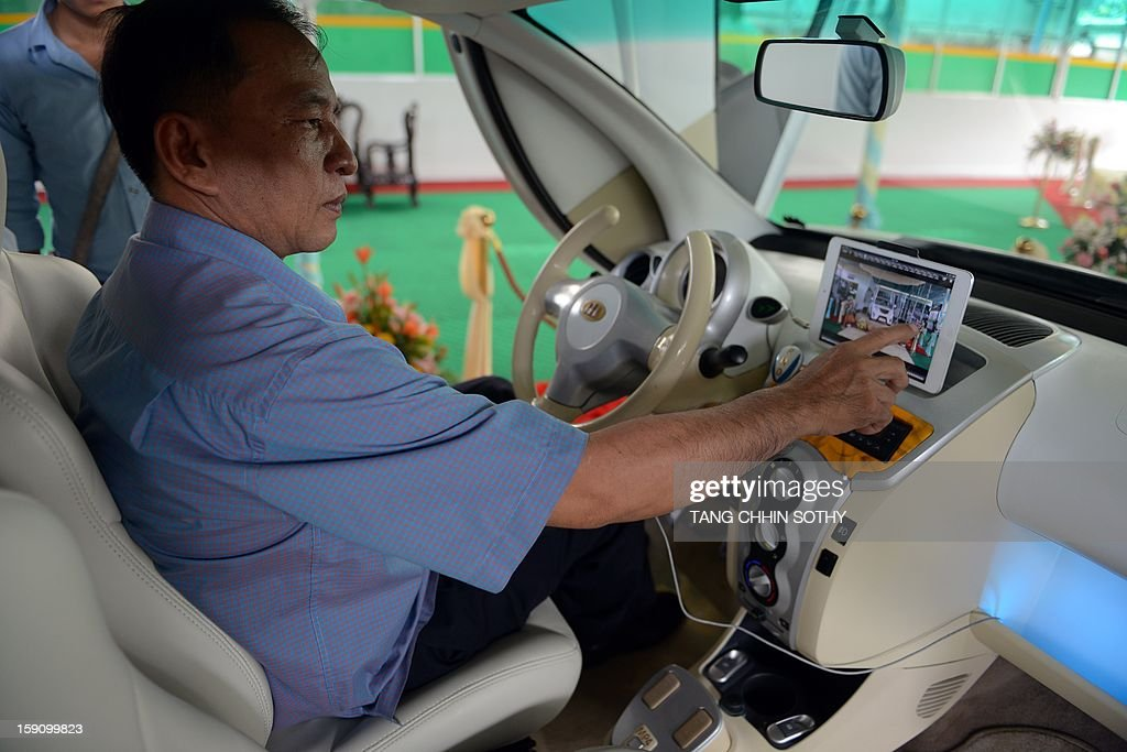 Cambodian mechanic Nhean Phaloek sits in a locally made electric car 'Angkor EV 2013' as he points at a feature for mobile tablet computers at a showroom in Phnom Penh on January 8, 2013. Cambodia's Heng Development Company has unvveilled its first electric-powered car branded 'Angkor', named after the country's famed ancient Angkor temples, which has a top speed of 60 kilometres per hour and was designed by local innovator Nhean Phaloek.