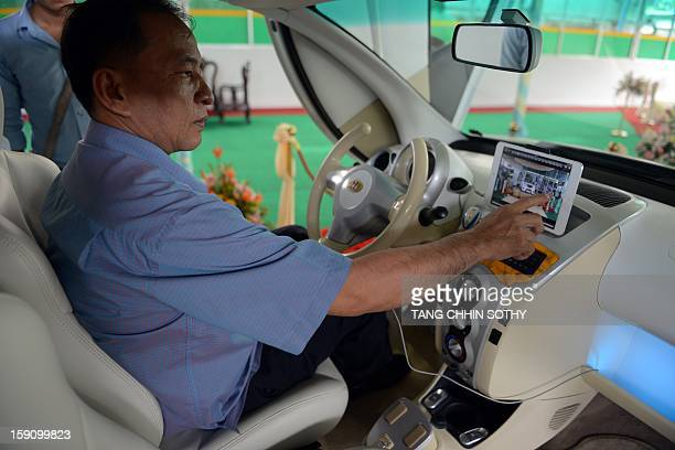 Cambodian mechanic Nhean Phaloek sits in a locally made electric car 'Angkor EV 2013' as he points at a feature for mobile tablet computers at a...