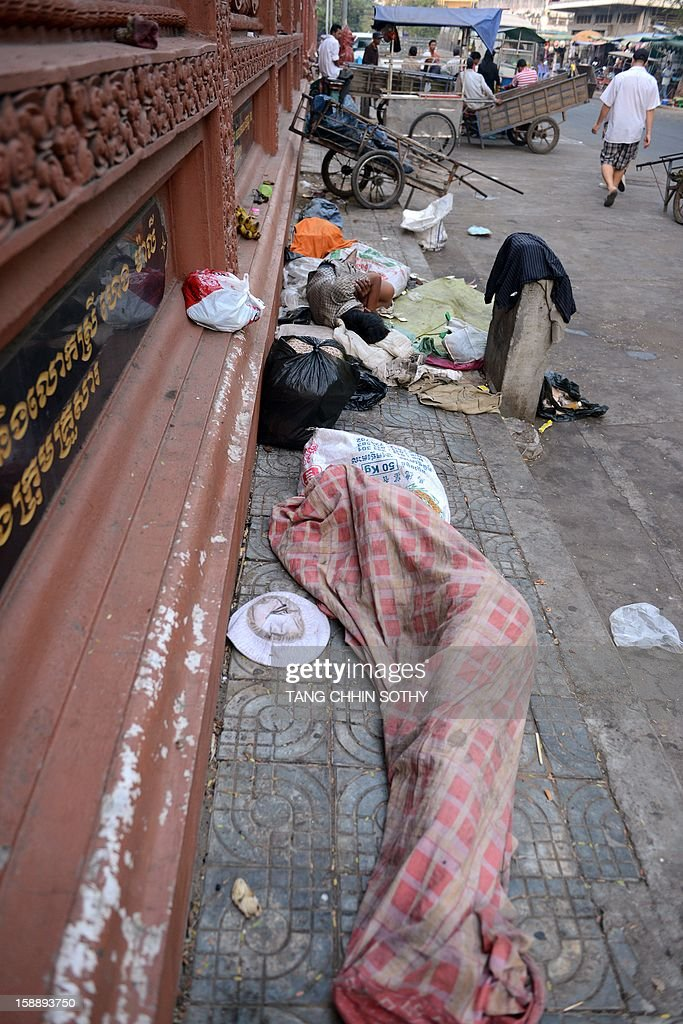 Cambodian men sleep near litter along a street in Phnom Penh on January 3, 2013. Written off as a failed state after the devastating 1975-1979 Khmer Rouge regime and several decades of civil war, Cambodia has used garment and footwear exports and tourism to help improve its economy, but remains one of the world's poorest countries with around 30 percent of its 14 million people living on less than a dollar a day.