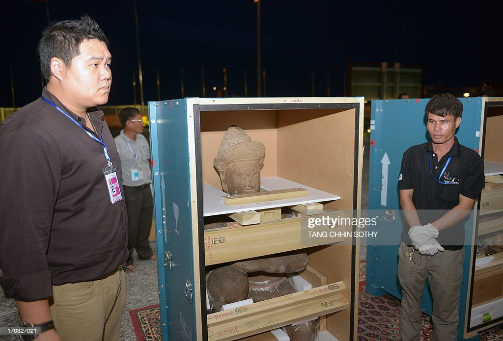 Cambodian men stand next to boxes holding 10th century statues upon their arrival at Phnom Penh International Airport on June 11, 2013. The two statues that Cambodia says were looted from a jungle temple several decades ago were returned home on June 11 from New York's Metropolitan Museum of Art, in what the kingdom described as a 'historic' moment.