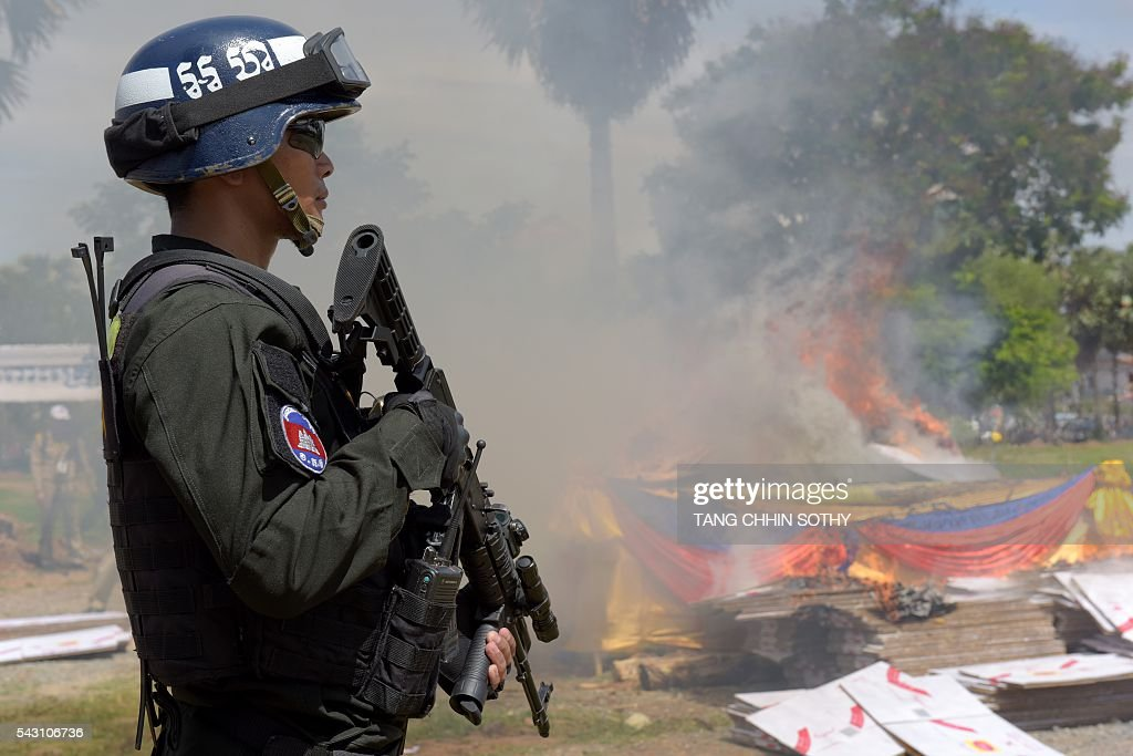 A Cambodian military police official stands guard near a burning pile of drugs during a destruction ceremony to mark the UN's 'International Day against Drug Abuse and Illicit Trafficking' in Phnom Penh on June 26, 2016. Cambodian authorities burned nearly 2 tons of seized drugs during the event. / AFP / TANG