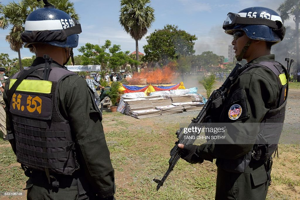 Cambodian military police officials stand guard near a burning pile of drugs during a destruction ceremony to mark the UN's 'International Day against Drug Abuse and Illicit Trafficking' in Phnom Penh on June 26, 2016. Cambodian authorities burned nearly 2 tons of seized drugs during the event. / AFP / TANG