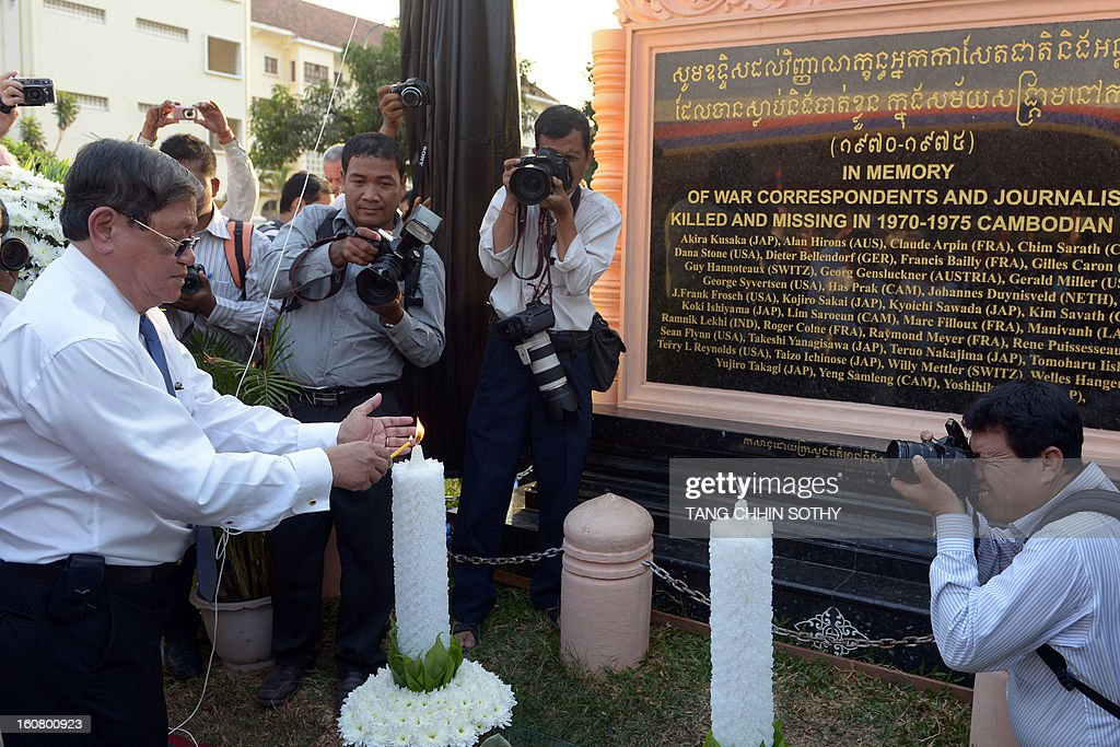 Cambodian minister of information and government spokesman Khieu Kanharith (L) lights a candle as he prays in front of a memorial sign at a park in front of the Le Royal hotel on February 6, 2013. Cambodia on February 6 officially unveiled a memorial to dozens of foreign and local journalists killed covering the country's 1970-75 war won by the communist Khmer Rouge regime. Led by 'Brother Number One' Pol Pot, who died in 1998, the Khmer Rouge wiped out nearly a quarter of the population through starvation, overwork or execution during its 1975-1979 rule in a bid to forge a communist utopia.