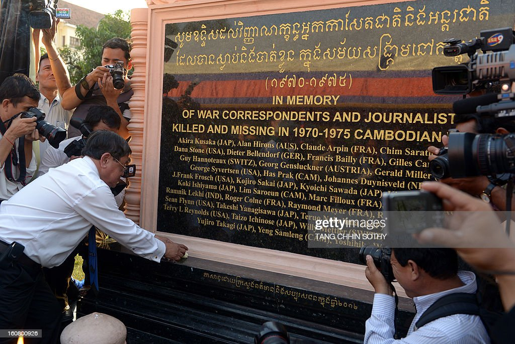 Cambodian minister of information and government spokesman Khieu Kanharith (L) lays a flower as he prays in front of a memorial sign at a park in front of the Le Royal hotel on February 6, 2013. Cambodia on February 6 officially unveiled a memorial to dozens of foreign and local journalists killed covering the country's 1970-75 war won by the communist Khmer Rouge regime. Led by 'Brother Number One' Pol Pot, who died in 1998, the Khmer Rouge wiped out nearly a quarter of the population through starvation, overwork or execution during its 1975-1979 rule in a bid to forge a communist utopia.