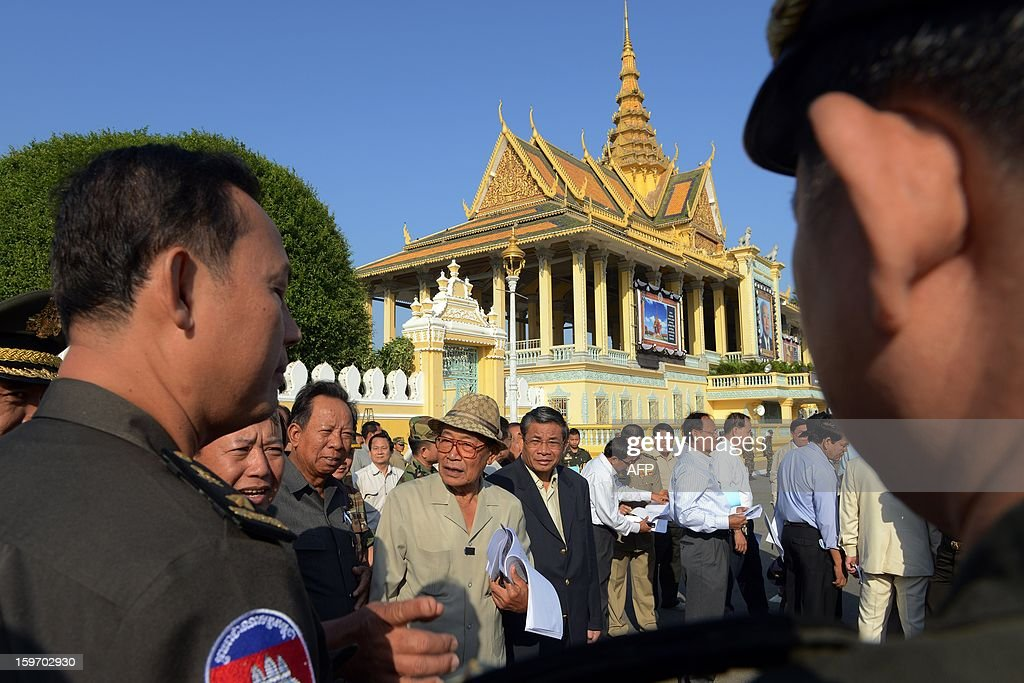 Cambodian Minister of the Royal Palace Kong Sam Ol (C) talks to Cambodian Minister of National Defense General Tea Banh (Center L) during a funeral march procession rehearsal for the late former King Norodom Sihanouk in front of the Royal Palace in Phnom Penh on January 19, 2013. Cambodia's beloved former monarch Norodom Sihanouk, who died aged 89 last month, will be cremated on February 4 following an elaborate ceremony, Cambodian Prime Minister Hun Sen said on November 26, 2012.