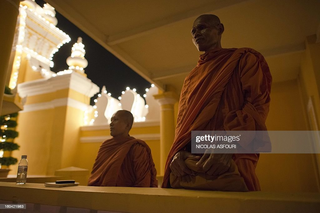 Cambodian monks come to pay their respect for the late former King Norodom Sihanouk in front of the Royal Palace in Phnom Penh on January 31, 2013 ahead of a lavish funeral procession on February 1 which will see his body carried from the royal palace in Phnom Penh to a funeral pyre in a nearby park and is expected to draw more than one million mourners to the capital's streets. Sihanouk, who abdicated in 2004 after steering Cambodia through six decades marked by independence from France, civil war, the murderous Khmer Rouge regime and finally peace, died of a heart attack in Beijing on October 15, 2012 and will be cremated on February 4. AFP PHOTO/ Nicolas ASFOURI