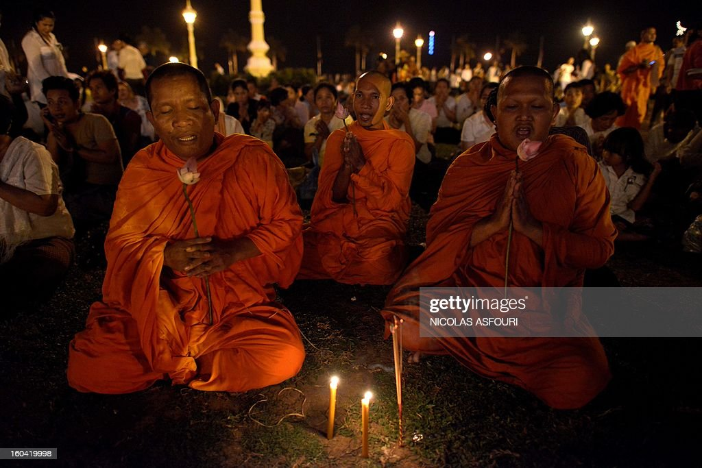 Cambodian monks pray for the late former King Norodom Sihanouk in front of the Royal Palace in Phnom Penh on January 31, 2013 ahead of a lavish funeral procession on February 1 which will see his body carried from the royal palace in Phnom Penh to a funeral pyre in a nearby park and is expected to draw more than one million mourners to the capital's streets. Sihanouk, who abdicated in 2004 after steering Cambodia through six decades marked by independence from France, civil war, the murderous Khmer Rouge regime and finally peace, died of a heart attack in Beijing on October 15, 2012 and will be cremated on February 4. AFP PHOTO/ Nicolas ASFOURI