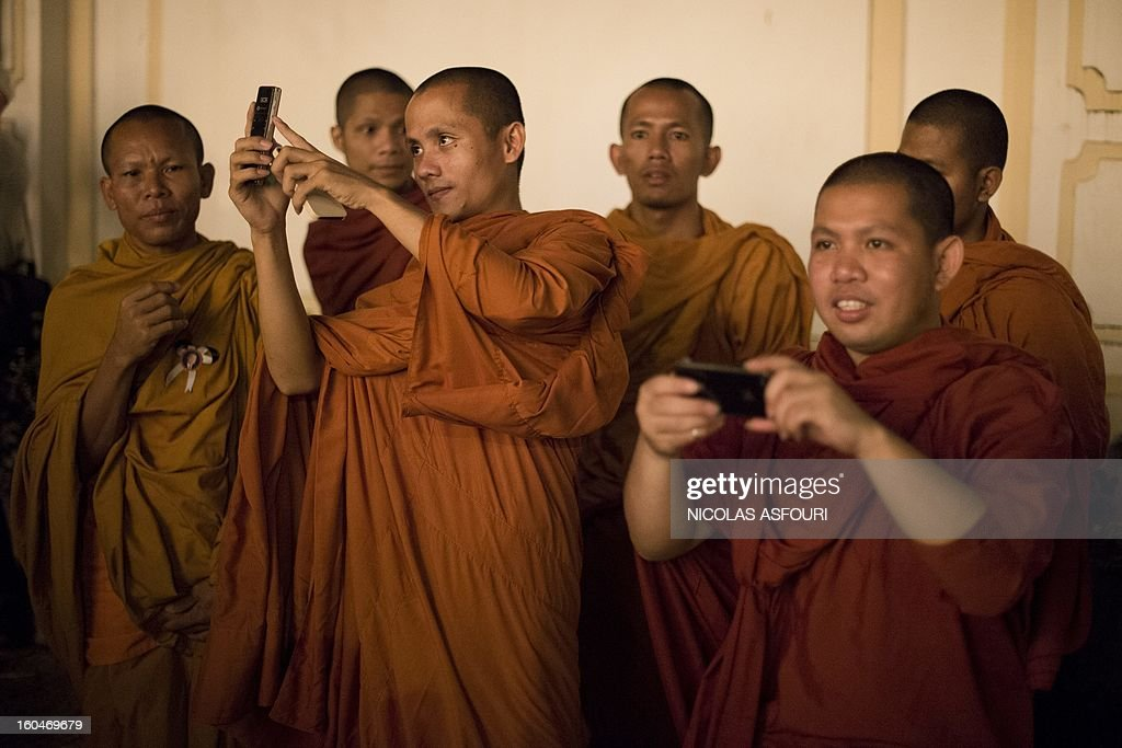Cambodian monks take pictures with their mobile phones as they come to pay their respects to the late former King Norodom Sihanouk in front of the Royal Palace in Phnom Penh on February 1, 2013 as a sea of mourners filled the streets of the Cambodian capital for a lavish funeral for the revered former king. Sihanouk, who abdicated in 2004 after steering Cambodia through six decades marked by independence from France, civil war, the murderous Khmer Rouge regime and finally peace, died of a heart attack in Beijing on October 15, 2012 and will be cremated on February 4. AFP PHOTO / Nicolas ASFOURI