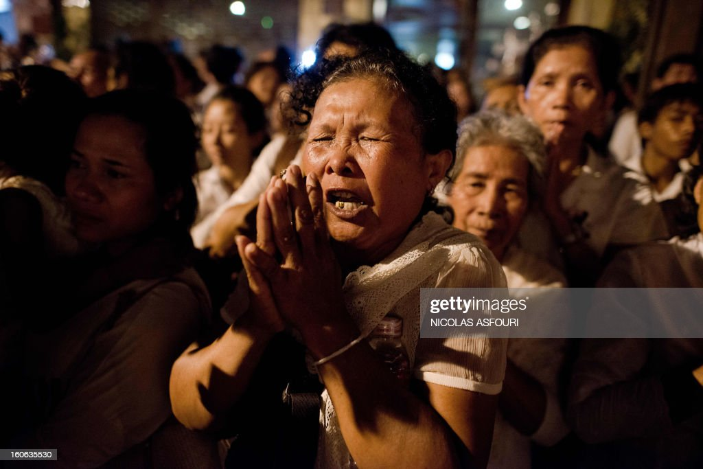Cambodian mourners cry and pray as smoke rises out from the roof the crematorium during the cremation where a coffin bearing the remains of Cambodia's late King Norodom Sihanouk is placed, near the Royal Palace in Phnom Penh on February 4, 2013. Thousands of mourners massed in the Cambodian capital as the kingdom cremated its revered former King Norodom Sihanouk, who steered his country through six turbulent decades. AFP PHOTO/ Nicolas ASFOURI