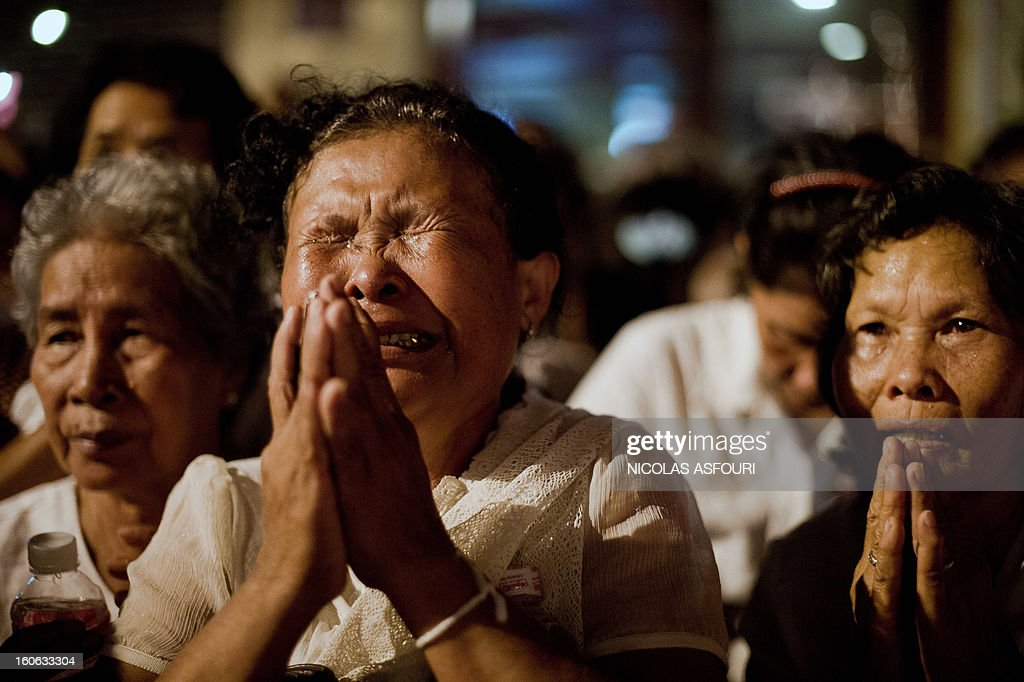 Cambodian mourners cry as smoke rises out from the roof the crematorium during the cremation where a coffin bearing the remains of Cambodia's late King Norodom Sihanouk is placed, near the Royal Palace in Phnom Penh on February 4, 2013. Thousands of mourners massed in the Cambodian capital as the kingdom cremated its revered former King Norodom Sihanouk, who steered his country through six turbulent decades. AFP PHOTO/ Nicolas ASFOURI
