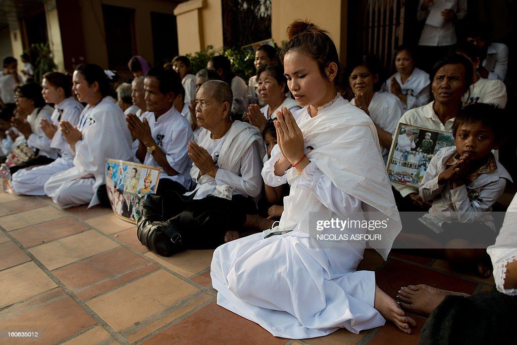 Cambodian mourners sit and pray in a street at the crematorium where a coffin bearing the remains of Cambodia's late King Norodom Sihanouk is placed before his cremation near the Royal Palace in Phnom Penh on February 4, 2013. Thousands of mourners massed in the Cambodian capital as the kingdom cremated its revered former King Norodom Sihanouk, who steered his country through six turbulent decades. AFP PHOTO/ Nicolas ASFOURI