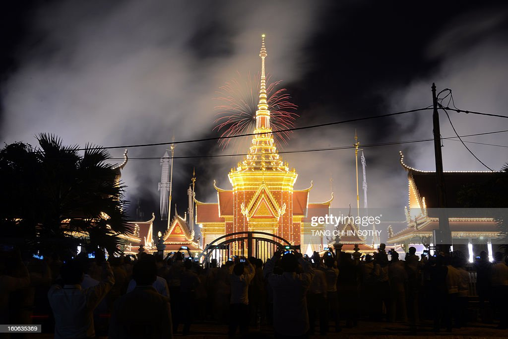 Cambodian onlookers watch as smoke rises from the crematorium to mark the beginning of the cremation where a coffin bearing the remains of Cambodia's late King Norodom Sihanouk is placed, near the Royal Palace in Phnom Penh on February 4, 2013. Thousands of mourners massed in the Cambodian capital as the kingdom cremated its revered former King Norodom Sihanouk, who steered his country through six turbulent decades. AFP PHOTO/ TANG CHHIN SOTHY