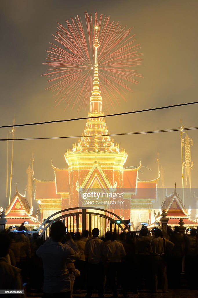 Cambodian onlookers watch fireworks as smoke rises from the crematorium during the cremation where a coffin bearing the remains of Cambodia's late King Norodom Sihanouk is placed, near the Royal Palace in Phnom Penh on February 4, 2013. Thousands of mourners massed in the Cambodian capital as the kingdom cremated its revered former King Norodom Sihanouk, who steered his country through six turbulent decades.