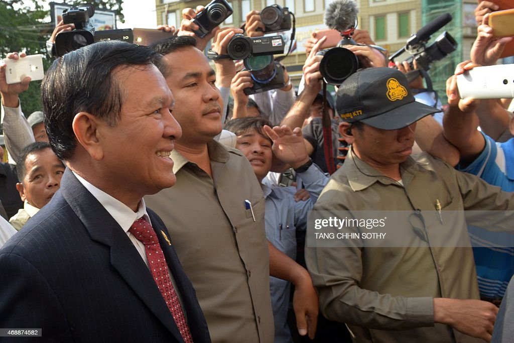 Cambodian opposition party deputy leader <a gi-track='captionPersonalityLinkClicked' href=/galleries/search?phrase=Kem+Sokha&family=editorial&specificpeople=659005 ng-click='$event.stopPropagation()'>Kem Sokha</a> (L) smiles as he walks into the Phnom Penh municipal court on April 8, 2015. Sokha appeared at a court for questioning over a demonstration after the general election in July 2013.
