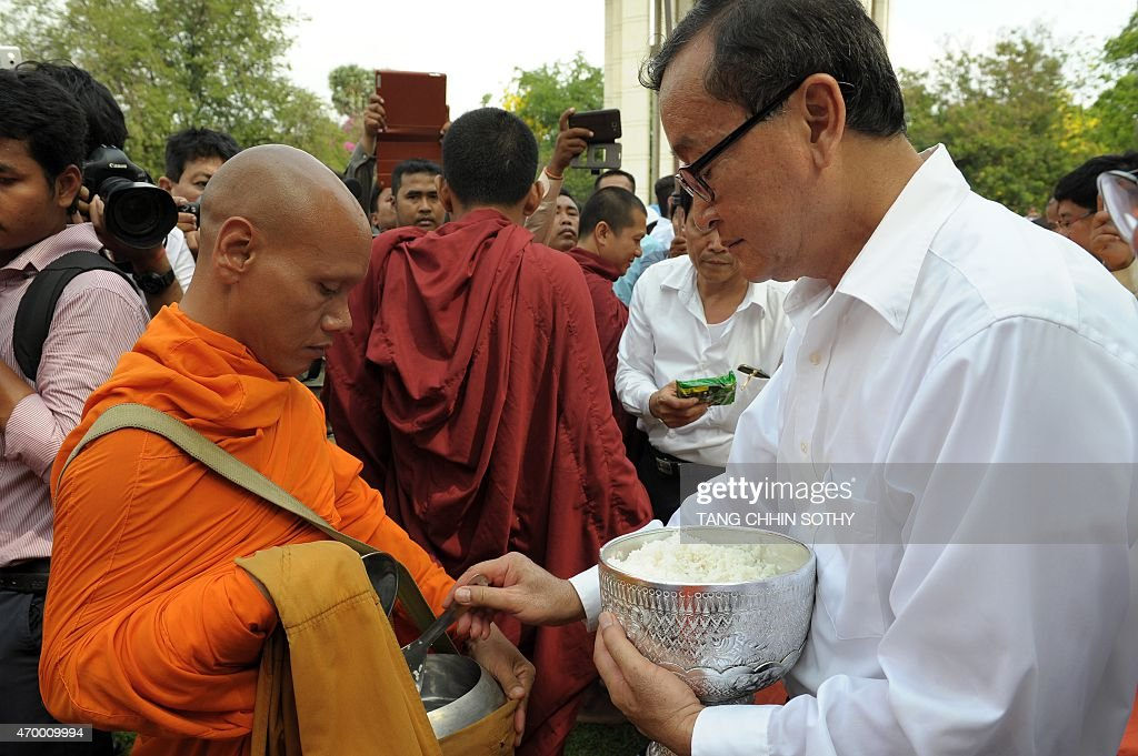 Cambodian opposition party leader Sam Rainsy offers food to a Buddhist monk at Choeung Ek killing fields memorial in Phnom Penh on April 17 2015...