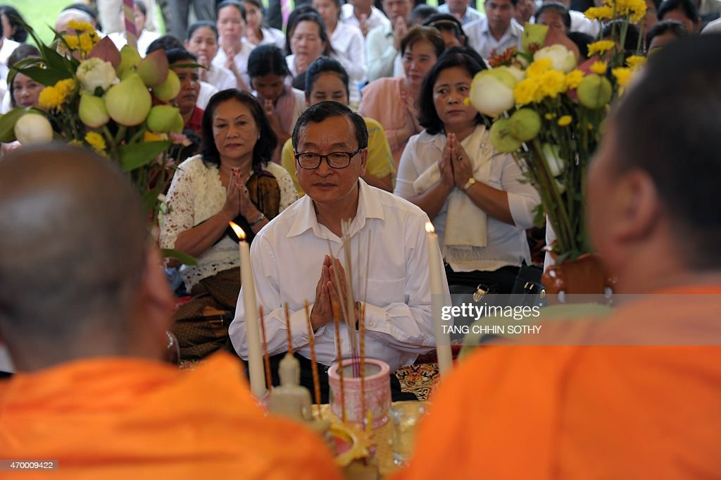 Cambodian opposition party leader Sam Rainsy prays in front of Buddhist monks at Choeung Ek killing fields memorial in Phnom Penh on April 17 2015...