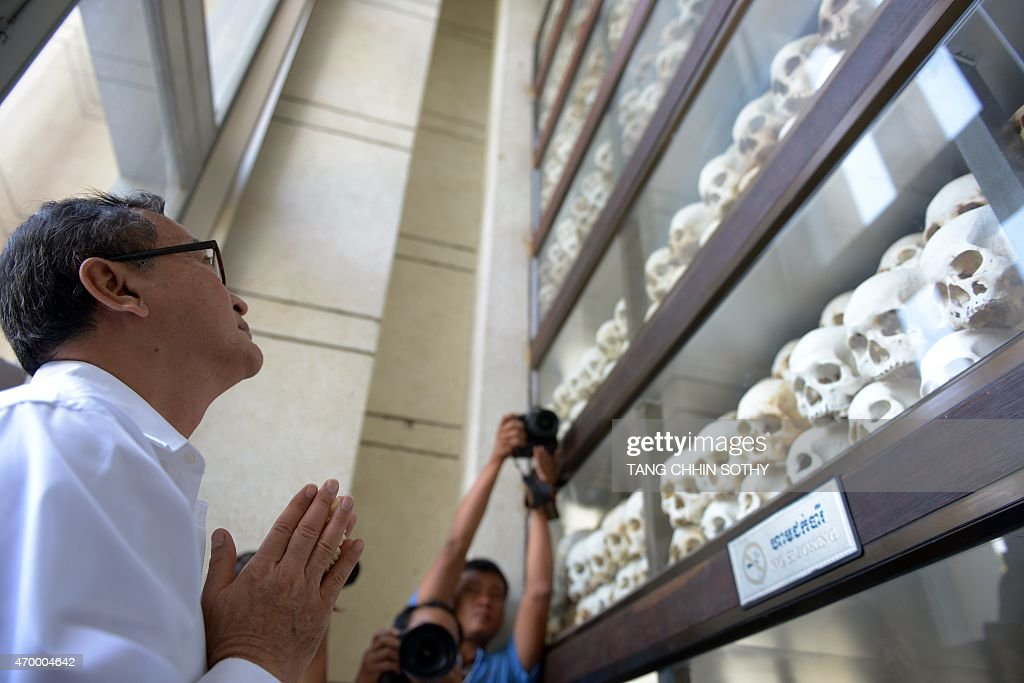 Cambodian opposition party leader Sam Rainsy prays in front of skulls at Choeung Ek killing fields memorial in Phnom Penh on April 17 2015 Tearful...