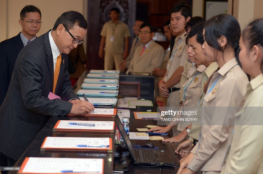 Cambodian opposition party leader Sam Rainsy signs his attendance for the National Assembly meeting in Phnom Penh on April 9 2015 Cambodia's...