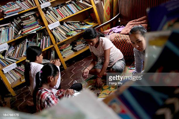 Cambodian orphans gather beside many books which donated by foreign volunteers in a nongovernment orphanage on September 28 2013 in Siem Reap...