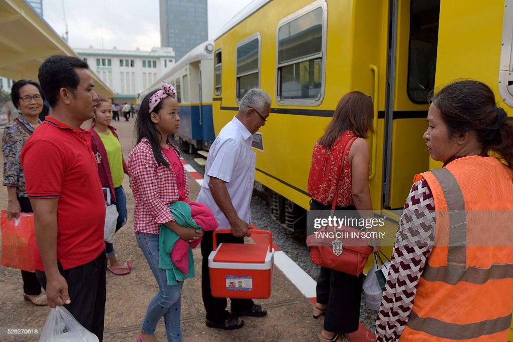 Cambodian passengers board a train at the Phnom Penh train station on April 30, 2016, as the railway service resumes after years of suspension. Cambodia's sole passenger train resumed a regular weekend service April 30 after years of suspension, with Prime Minister Hun Sen climbing aboard to inaugurate the first trip. The Southeast Asian country has more than 600 kilometres of railroad extending from its northern border with Thailand down to the southern coast, but decades of war and neglect have left vast stretches of track damaged. / AFP / TANG