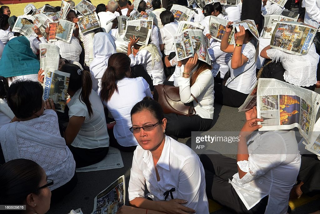 Cambodian people cover their heads with local newspapers as they wait to pray for the late former King Norodom Sihanouk at the cremation site near the Royal Palace in Phnom Penh on February 2, 2013. A sea of mourners filled the streets of the Cambodian capital on February 1, for a lavish funeral for revered former king Norodom Sihanouk, who towered over six tumultuous decades in his nation's history. AFP PHOTO/TANG CHHIN SOTHY