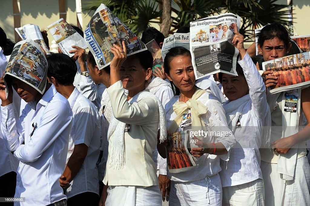 Cambodian people cover their heads with local newspapers as they wait to pray for the late former King Norodom Sihanouk at the cremation site near the Royal Palace in Phnom Penh on February 2, 2013. A sea of mourners filled the streets of the Cambodian capital on February 1, for a lavish funeral for revered former king Norodom Sihanouk, who towered over six tumultuous decades in his nation's history.