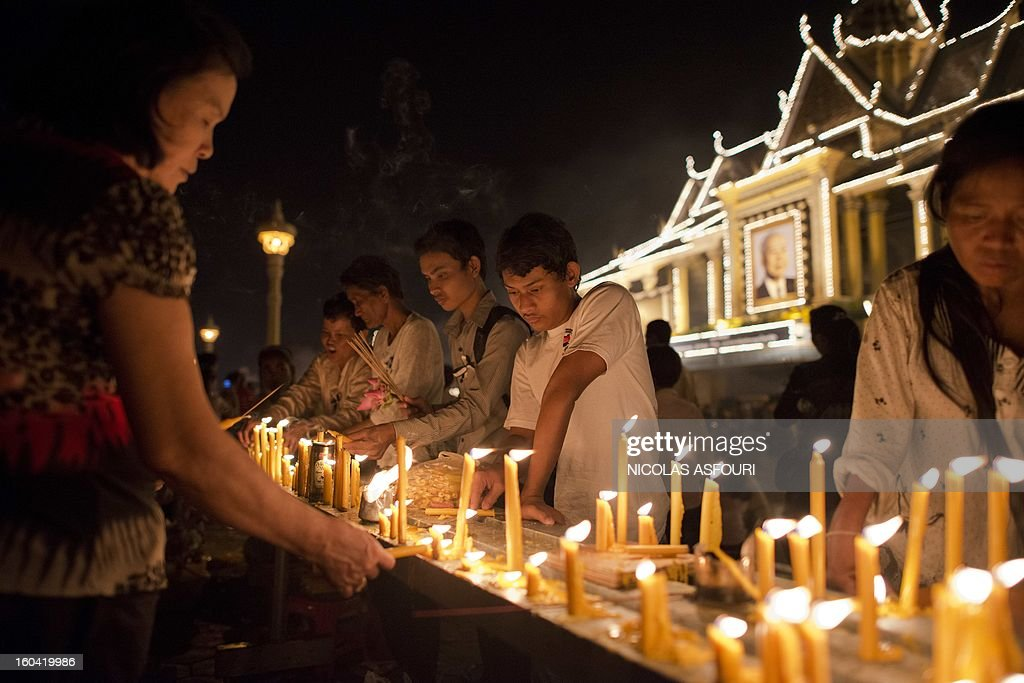 Cambodian people light candles for the late former King Norodom Sihanouk in front of the Royal Palace in Phnom Penh on January 31, 2013 ahead of a lavish funeral procession on February 1 which will see his body carried from the royal palace in Phnom Penh to a funeral pyre in a nearby park and is expected to draw more than one million mourners to the capital's streets. Sihanouk, who abdicated in 2004 after steering Cambodia through six decades marked by independence from France, civil war, the murderous Khmer Rouge regime and finally peace, died of a heart attack in Beijing on October 15, 2012 and will be cremated on February 4. AFP PHOTO/ Nicolas ASFOURI