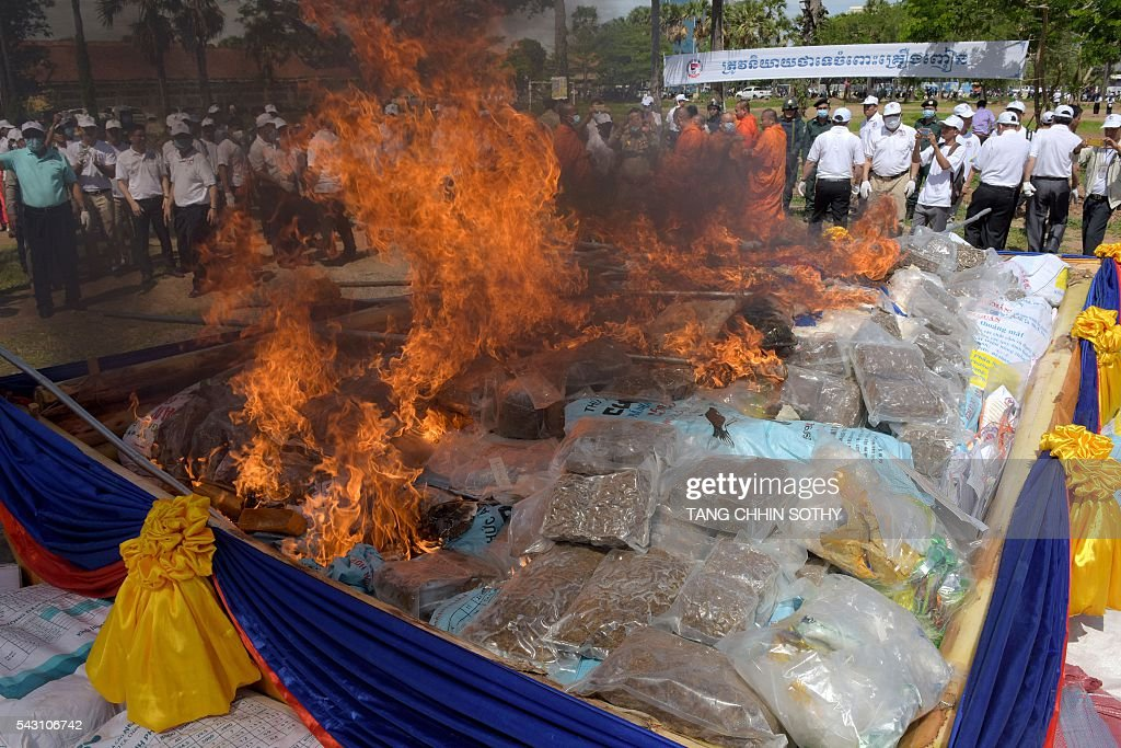Cambodian people look at a burning pile of drugs during a destruction ceremony to mark the UN's 'International Day against Drug Abuse and Illicit Trafficking' in Phnom Penh on June 26, 2016. Cambodian authorities burned nearly 2 tons of seized drugs during the event. / AFP / TANG
