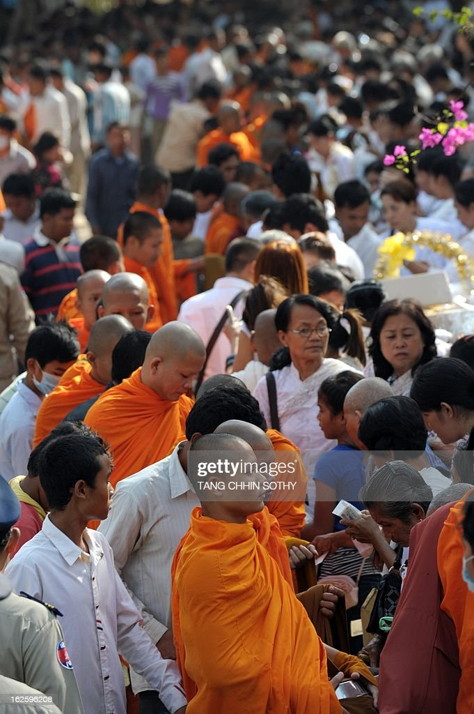 Cambodian people offer food to Buddhist monks during the Meak Bochea Buddhist celebration at the Oddong mountain in Kandal province, some 40 kilometers north of Phnom Penh on February 25, 2013. Thousands of Cambodian followers gathered at the temple for offerings to hundreds of Buddhish monks to mark Meak Bochea day, which marks when Buddha declared he would die in three months.