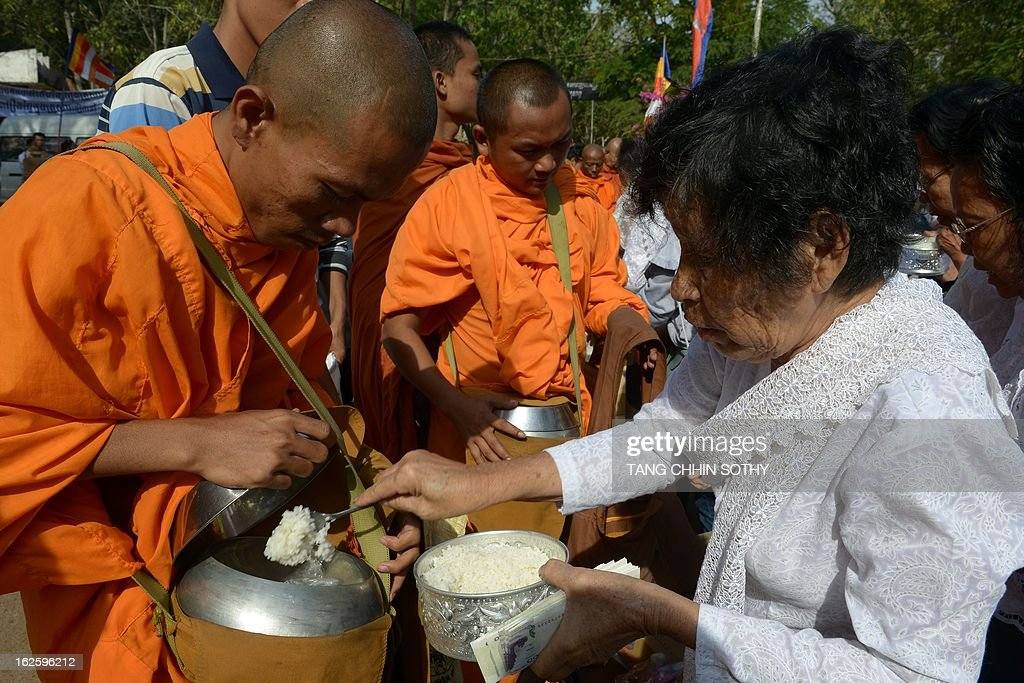 Cambodian people offer food to Buddhist monks during the Meak Bochea Buddhist celebration at the Oddong mountain in Kandal province, some 40 kilometers north of Phnom Penh on February 25, 2013. Thousands of Cambodian followers gathered at the temple for offerings to hundreds of Buddhish monks to mark Meak Bochea day, which marks when Buddha declared he would die in three months. AFP PHOTO / TANG CHHIN SOTHY